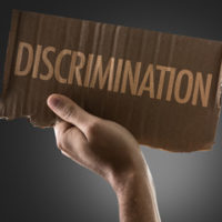 cardboard sign that says discrimination