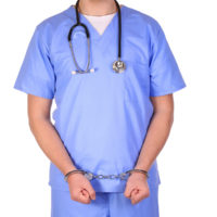 Doctor with stethoscope in handcuffs isolated on white