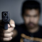 Man is shooting a gun , selective focus on front gun,use for add text