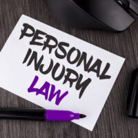 Handwriting text writing Personal Injury Law. Concept meaning guarantee your rights in case of hazards or risks written on White Sticky Note Paper on the wooden background Mouse Markers