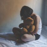 concept photo of Sexual assault, young girl sit on a bed in a bedroom.
