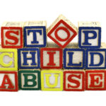 The words Stop Child Abuse in colorful wooden blocks 1/2