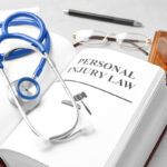 Book with words PERSONAL INJURY LAW and stethoscope on table