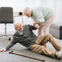 old woman helping to stand up husband who falled down on floor