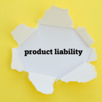 PRODUCT LIABILITY word written under torn paper.