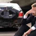 Desperate man sitting asphalt on crashed car background, automobile accident