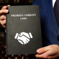 Lawyer holds PREMISES LIABILITY LAWS book. Apremises liabilitylawsuit holds apropertyowner responsible for any damages arising out of an injury on that person