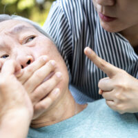Angry asian woman covering senior mouth and showing silence gesture, keep a secret be quiet,social violence,aggression, scared elderly people with female caregiver,bad relationship,physical abuse